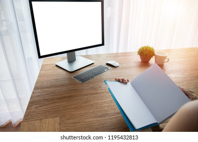 wood office table with blank screen on monitor and businessman reading a book.