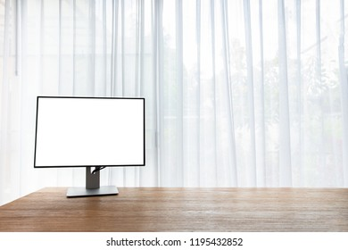 wood office table with blank screen on monitor on curtain window at home. view from office table.