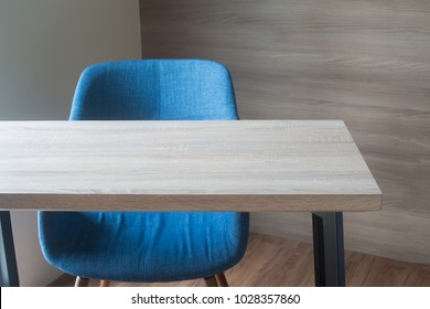wood office table with blue chair on wood wall background texture at working room. view form front office table.