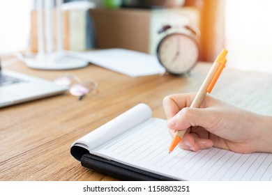 wood office table with businessman writing on notepad paper.