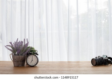 wood office table with classic clock and camera on white curtain backdrop background.