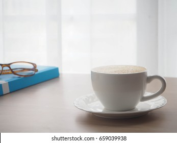 wood office table with cup of latte coffee and modern eyeglasses on blurry white curtain texture background, view from front wood table.