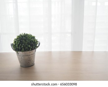 wood office table with free copy space for text and  small garden tree on pot on white drape texture background on sunny day. view from front  office table.