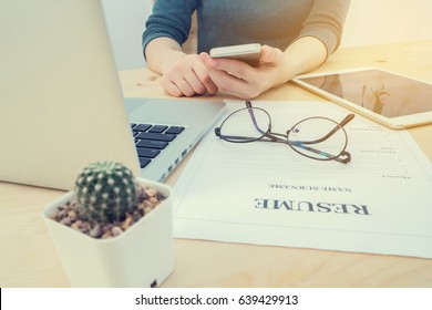 wood office table with human hand hold smartphone, tablet, cell phone with resume information, laptop and cactus flower on pot. concept of job search online. view form front office table.