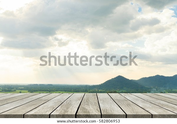 Wood old table against landscape mountain and cloud sky background at Sunset in the evening. For your product placement or montage with focus to the table top in the foreground