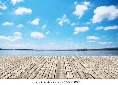 Wood old table against scenic view of the reservoir and blue sky. For your product placement or montage with focus to the table top in the foreground