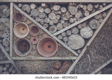 Wood on a shelf in a woodshed with pots and hay