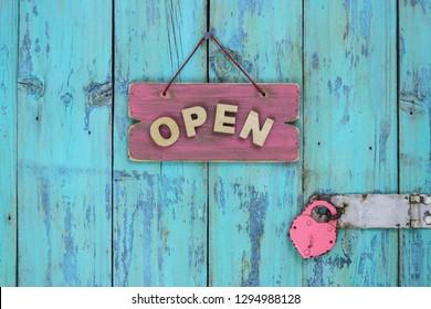 Wood OPEN sign hanging on rustic teal blue wooden door with heart