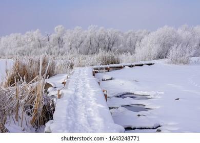 Wood path over Purgatory Creek in Winter in Minnesota