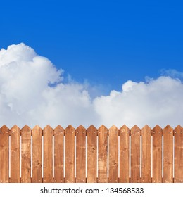 Wood picket fence with blue sky background