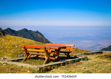 Wood picnic table and benches on top of the mountain with beautiful panoramic view at Balea Lake in Sibiu County, Romania