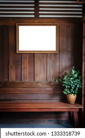 wood picture frame hang on wood wall background with plant vase