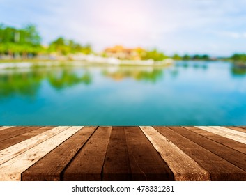 Wood pier or an old wooden table with blur image of lake and clear sky in background