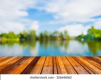 Wood pier or walkway or an old wooden table with  blur image of lake and sunset sky in background