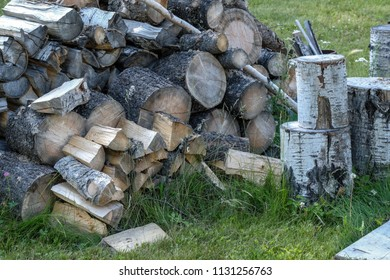 A wood pile with various types of firewood some of which are ready for the fire pit.