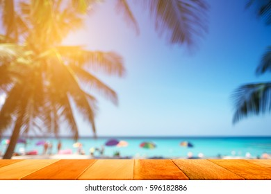 Wood plank with blurred sea and coconut tree background. Concept of beach in summer.