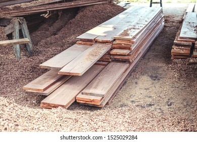 Wood plank with many shavings and sawdust at wood planer sawmill.