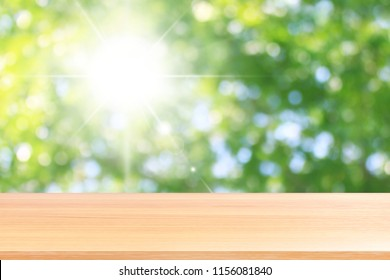 wood plank on lighting beautiful glittering green bokeh background, empty wood table floors on sunshine lighting green nature forest bokeh, wood table board empty front green glitter background light