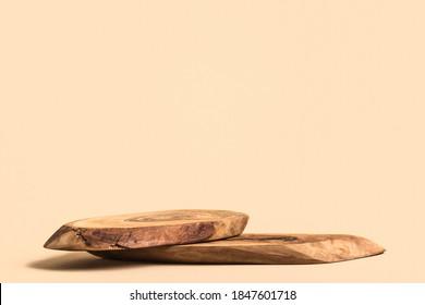 Holzpodest auf beigem Hintergrund für Kosmetikartikel.