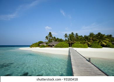 A wood pontoon access to paradise beach of a tropical island