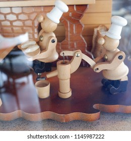WOOD POPPETS DISPLAY OF COOKS AND BAKERS IN WORK, BEHIND GLASS