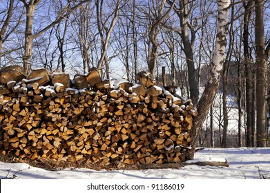 Wood prepared for winter in snowy forest in Pohorje, Slovenia