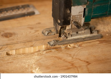 Wood processing. Person cutting wooden board with electric jigsaw.