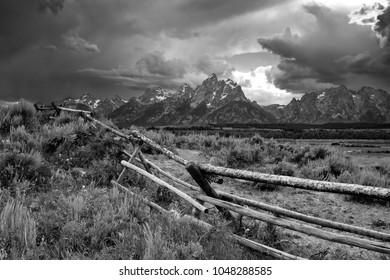 Wood rail fence frames an afternoon thunderstorm over Teton Mtns in Grand Teton National Park, Wyoming in black & white