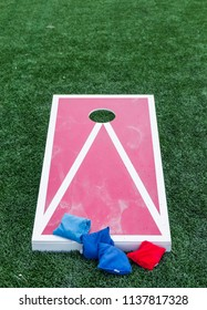 A wood red and white corn hole board is set up on a green turf field with blue and red bean bags.