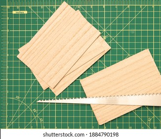 Wood saw on green cutting board with balsa wood pieces.