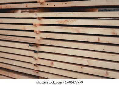 Holz und Sägewerk. Große Rundholze, die für den Bau geerntet wurden. Herstellung und Verkauf von Baustoffen. Gestapelte Bretter und Protokolle. Die Struktur des Holzes.