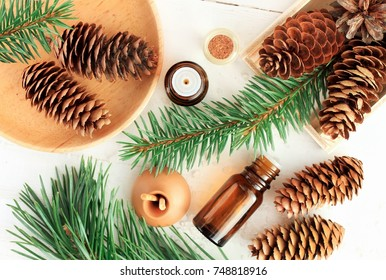 Wood scents for winter time aromatherapy. Pine cones and fresh green fir tree boughs, essential oil bottles, top view