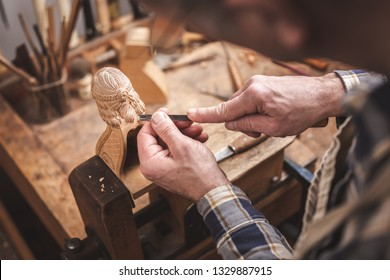 Wood sculptor at a workbench carving a wooden figure