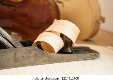 Wood shaving curled around carpentry plane used for making Cello or, violoncello