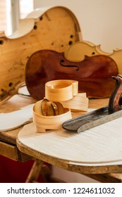 Wood shaving curls and carpentry plane used for making Cello or, violoncello, with semi assembled cello in background