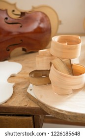 Wood shaving curls on table, and Cello or, violoncello, in background of craftsman's workshop