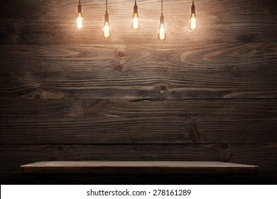 Wood shelf, grunge industrial interior with edison light bulb