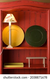 Wood shelf painted red with a pair of green and yellow sous plat, and a lamp