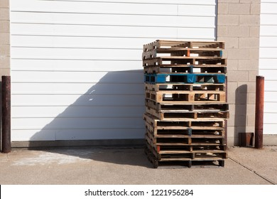 Wood Shipping Pallets Stacked Against Building Garage Door