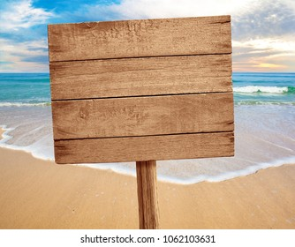 wood sign on beach background