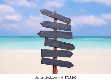 Wood signs on the beach. Sea and blue sky background blur