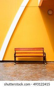 wood sofa is in front of yellow wall