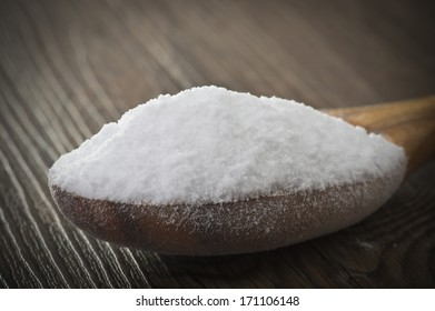 wood spoon of baking soda close up on table