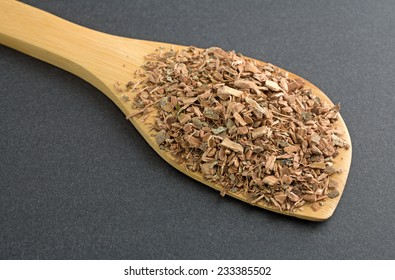 A wood spoon filled with a portion of witch hazel bark on a dark background.