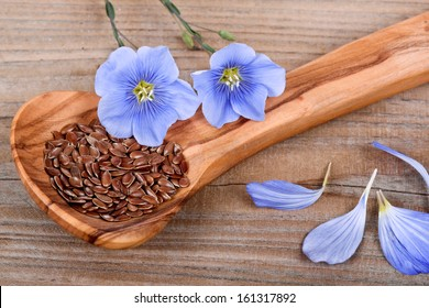 'Wood spoon with flaxseed and linum blossoms