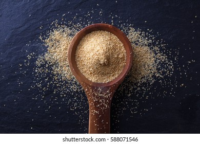 Wood spoon with garlic powder over a black stone table