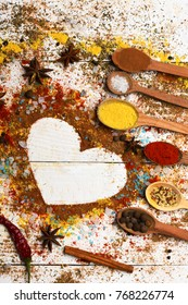 Wood spoons with turmeric, paprika, sea salt, cinnamon, anise and scattered seasoning. Set of spices on white wood background. Composition of condiment making heart shape. Cuisine and flavours concept