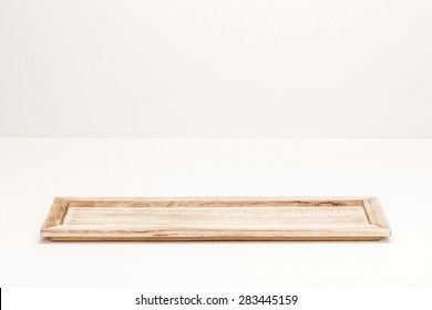 A wood square tray natural concept on the white table isolated white at the studio.