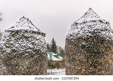wood stacked in a dome shape, with snow.