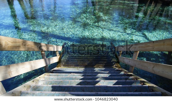 Wood stairs going down in to the turquoise clear water of the spring in Ginnie Springs, Florida